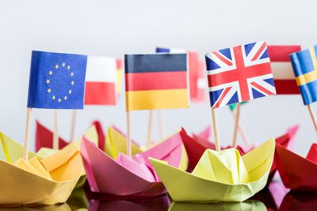 comercio: barcos de papel con diferentes banderas están construyendo una flota