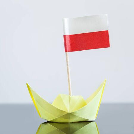 bandera de polonia: barco de papel con la bandera polaca, el concepto de env�o o tratado de libre comercio Foto de archivo