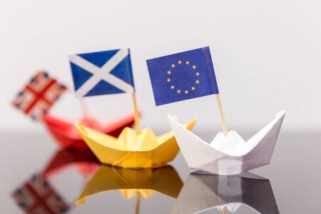scotish: paper ship with european and scots flag, broken british flag behind,  concept shipment or free trade agreement and membership of eu, independence referendum, scoxit or scexit