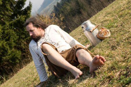 shoeless: a long-haired escapist with milk can and bread in the nature Stock Photo