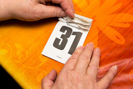 31: Senior adults hands with calendar 31 December