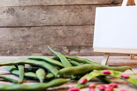 french bean: garden beans on a wooden table with empty board