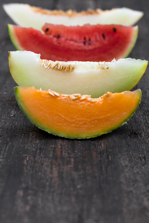 four different slices of melons on a wooden table