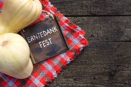 Butternut Pumpkins and Board on wooden Table, German Text Erntedankfest on it, which means Thanksgiving