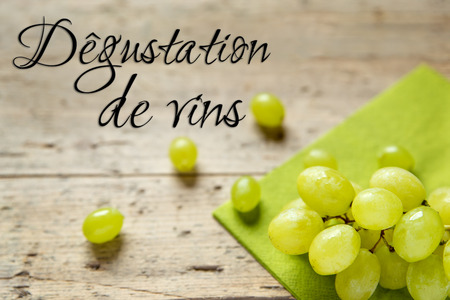 vins: White grapes on wooden table, french text Degustation de vins, which means wine tasting Stock Photo