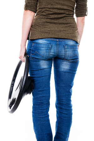 backview: woman with steering wheel is standing in front of white, backview Stock Photo