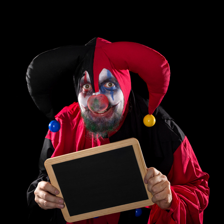 madly: madly Jester holding a slate with copyspace, black background