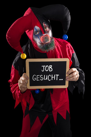 job market: a sadly clown holding a slate with german text job wanted, concept unemployement and job market