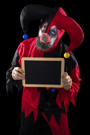 a sadly clown holding a slate with copyspace, black background