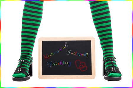 goblins: witch or goblin�s green and black striped legs, slate with german words for carnival, isolated on white