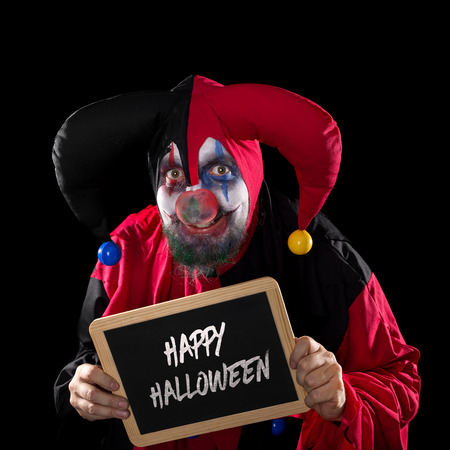 madly: madly Jester holding a slate with text happy halloween, black background