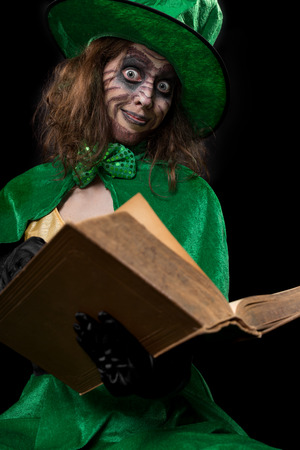 avarice: funny goblin girl is reading from a book, concept fairytales and myth, black background Stock Photo