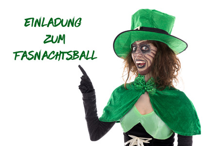 Funny green goblin showing on german text for a Invitation to carnival, isolated on white