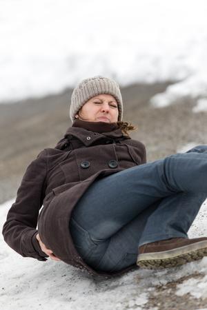 젊은 여자는 얼음 길, 허리 통증에 누워있다