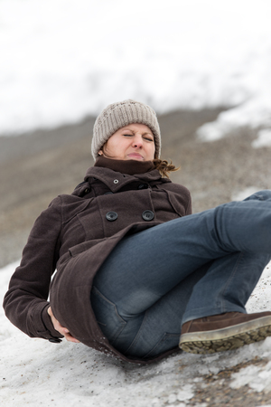warning back: young woman is lying on a ice way, pain on the back