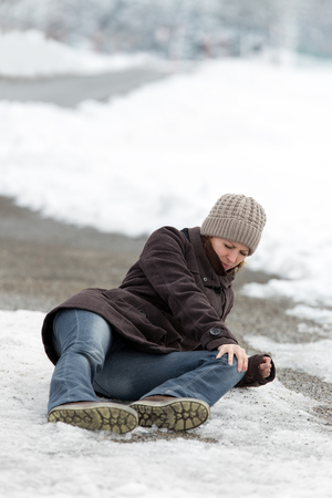 overthrow: young woman with a accident on a icy street, concept black ice und glaze Stock Photo