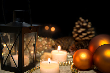 christmas balls, candles, a lantern and pearls on wooden table, black background