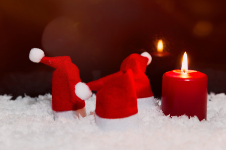 Red pointed hats and candle in the snow, red background, copyspace