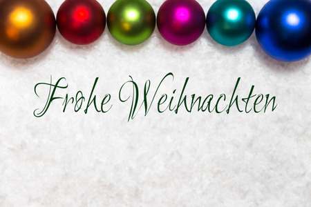 colorful christmas balls in the snow, german words frohe weihnachten, which means merry christmas
