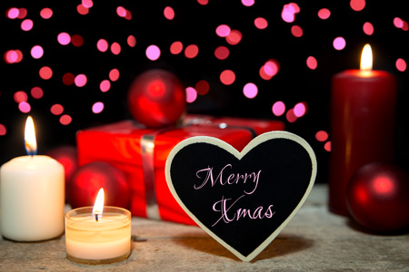 bougie coeur: festive card with candles, a present and christmas balls, heart with text merry xmas