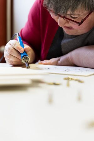 retardation: mentally disabled woman is doing woodburning with burning pen as art therapy, vertical