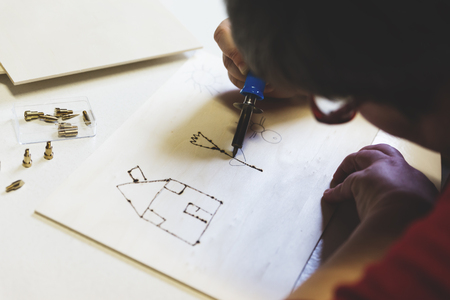 retardation: mentally disabled woman is doing woodburning as art therapy, horizontal Stock Photo