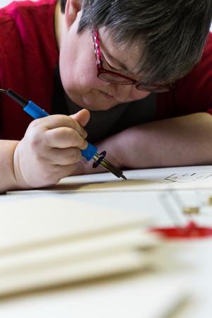 retardation: mentally disabled woman is doing woodburning as art therapy, vertical Stock Photo