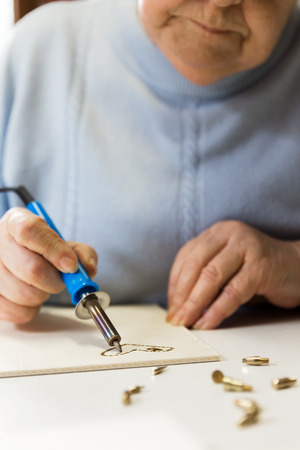 senior adult woman is doing woodburning as art therapy, vertical photo