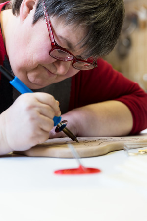 retardation: mentally disabled woman is doing woodburning as art therapy