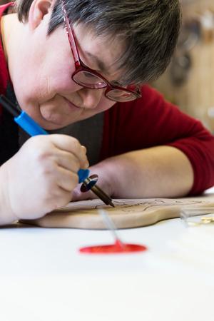 mentalmente mujer con discapacidad está haciendo leña como terapia de arte