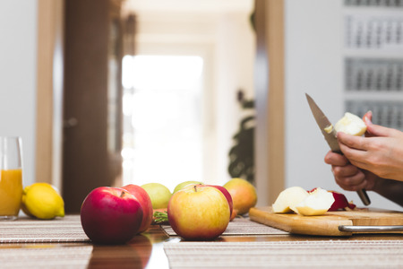 biologically: healthy nutrition, fresh fruits and vegetables, woman cutting apples Stock Photo
