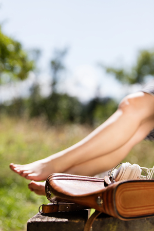 break in the nature, leather bag and headphone in the front, barefoot