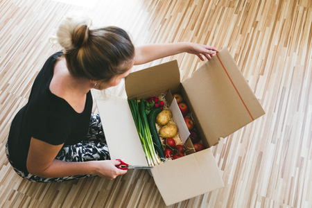 delivery: woman opening a vegetable delivery box at home, online ordering