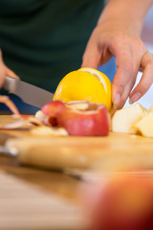 biologically: woman cutting a fresh lemon, apples in the front, concept vitamin c