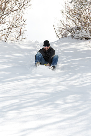 slump: a laughing man sledging in deep snow, concept winter and sleigh ride