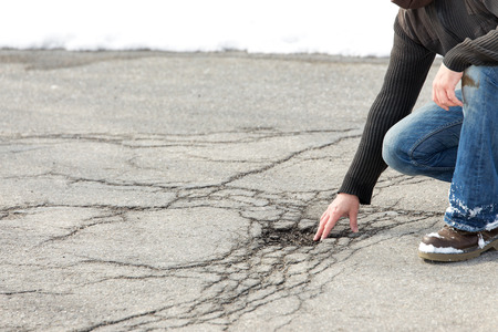 male inspector controlling road damage with potholes based on frost and winter