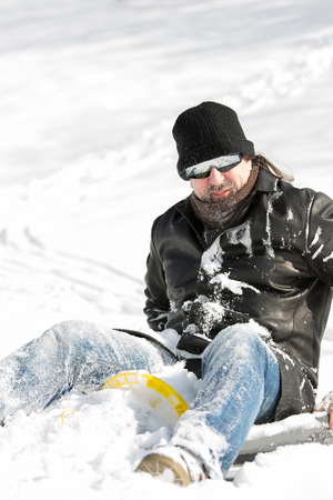 sledging people: Portrait of a cool man full of snow sitting on a slegde in deep snow