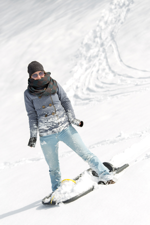young smiling woman with a sled standing in the deep snow Stock Photo