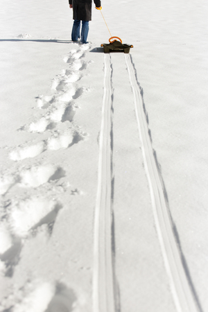 sledging people: a man pulling a sledge in the deep snow, footprints and tracks Stock Photo