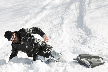 sledging people: a man slumping in the deep snow after a sleigh ride with a sledge