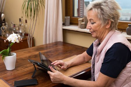 senior adult woman: smiling senior adult woman with tablet, in living room with table