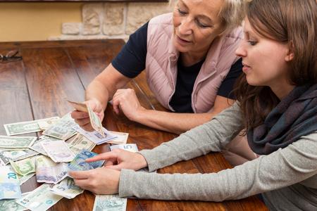 banco dinero: madre e hija con gran cantidad de monedas sobre una mesa