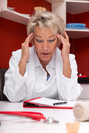 nursing record: aged femlae doctor with headache, maybe burnout, documents on a table, red office