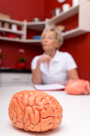 aged female doctor, in front a plastic brain, red surgery Stock Photo