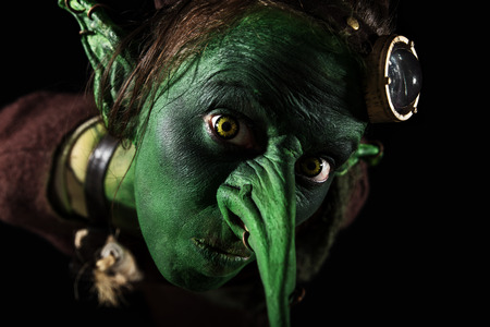 closeup, green female goblin with a long nose and freaky ears, Halloween or carnival theme Stock Photo
