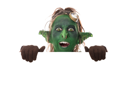 funny green goblin looking across white copyspace, isolated