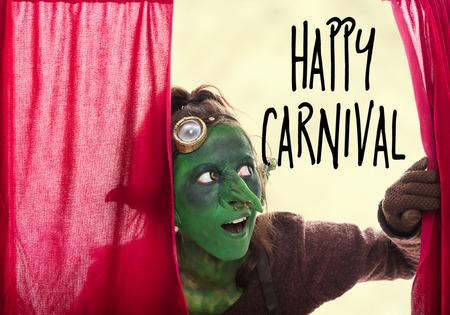 goblin: green goblin behind a red grand drape, english text happy carnival Stock Photo