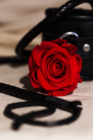 bdsm roleplay toys with a red rose on a white blanket Stock Photo