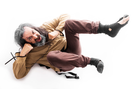 insane man with straitjacket, lays on the floor Stock Photo