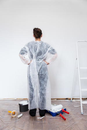 the emancipation: woman with fresh painted white wall, ladder and painting tools Stock Photo